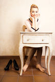 Vintage style. Barefoot girl sitting at retro desk Royalty Free Stock Image
