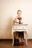 Vintage style. Barefoot girl sitting at retro desk stock photography