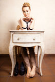 Vintage style. Barefoot girl sitting at retro desk Royalty Free Stock Photography