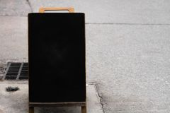 Vintage style blackboard Located on the footpath near the road stock illustration
