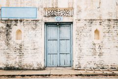 Vintage brick wall and sky blue wooden door, old Indian house