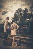 Vintage style couple. Beautiful vintage style couple with suitcases on  train station platform Royalty Free Stock Image