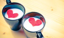 Vintage style of cup of milk with decorative hearts on wood table, concept of valentine day Stock Photography