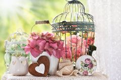 Vintage style decoration with flowers and bird cages. Vintage style decoration with flowers,bird cages and laces on the table in the garden stock photography