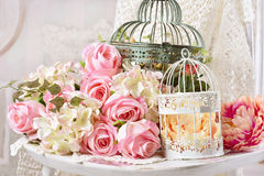 Vintage style decoration with flowers in old bird cages Stock Photos