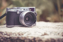 Vintage-style digital camera on boulder over blurred nature back Stock Image