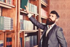 Vintage style and fashion. Bearded man in expensive suit in his cabinet. Professor stands in big library and holds book royalty free stock photography