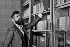 Vintage style and fashion. Bearded man in expensive suit in his cabinet. Professor stands in big library and holds book royalty free stock photo