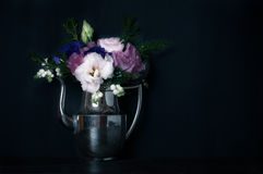 Vintage style, floral decorations. Summer bouquet of purple and pink eustomas in an antique coffee pot on a black background, vintage style, floral decorations Royalty Free Stock Photo