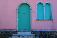 Blue door and windows against pink wall. Vintage style home front door and classical windows frame Royalty Free Stock Photography