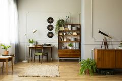 Vintage style home office with desk with typewriter and bookshelf next to it, real photo. Horizontal view royalty free stock photos