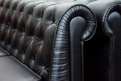 Vintage style of interior decoration the black leather sofa. Selective focus Royalty Free Stock Photo
