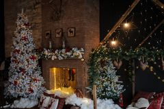 Vintage style interior of fireplace with christmas tree. Vintage chair, artificial snow, beautiful bed stock photos