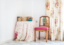 Vintage style interior with table, carved chair and floral curtain Stock Photo