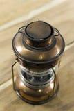 Vintage style kerosene lamp, lantern. On wood background Stock Photography