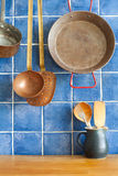 Vintage style kitchen accessories. Old utensils pan ladle pitcher with spoon, spatula. Wooden table and blue tile Royalty Free Stock Images