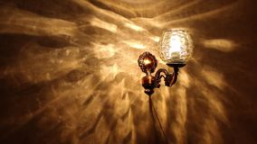 Vintage style lamp illuminating dark wall background, Retro lamp turning on and off stock video footage