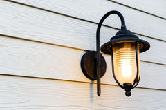 Vintage style lamp light bulb hang on white urban wall Royalty Free Stock Photography
