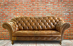 Vintage style  leather sofa with wooden floor and brick wall Stock Photo