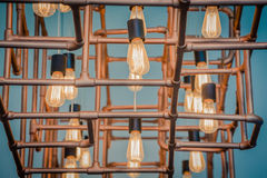 Vintage style light bulbs. Hang and decorated with alloy pipes in a living room with vintage blue tone Royalty Free Stock Photos