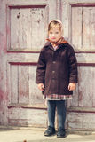 Vintage style. Little cute girl on the background of the old doo Royalty Free Stock Photos