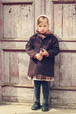 Vintage style. Little cute girl on the background of the old doo Stock Photos