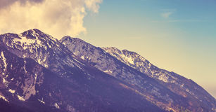 Vintage style looking view to rock snowbound mountains Royalty Free Stock Photography