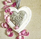 Vintage style ornamental wooden white heart, with pink rose buds and on textile surface, shabby chic and romantic.  Royalty Free Stock Photo