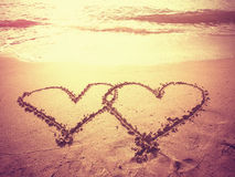 Vintage style photo of two hearts shape draw on the beach. Royalty Free Stock Images