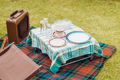 Vintage style picnic setup on grass. Vintage style picnic setup with antique items and radio on grass royalty free stock images
