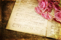 Vintage style picture of roses and music notes. Background picture with vintage style texture of a rose bouquet on old sheets of music Royalty Free Stock Photography