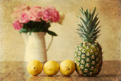 Vintage style picture of a still life with pineapple. Vintage style still life picture of a pineapple with three lemons in a row on a wooden table and a rose royalty free stock image