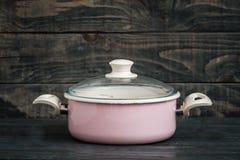 Vintage Style Pink Enamel Saucepan on Blue Wooden Background Royalty Free Stock Image