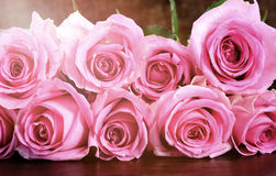Vintage style pink roses on rustic dark wood table. Royalty Free Stock Images