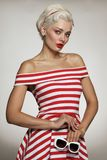 Vintage style portrait of young beautiful blond woman in striped. Dress Royalty Free Stock Image