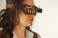 Vintage style researcher mechanist of the monocle with a large number of lenses looking at something royalty free stock image