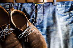 Vintage style shoes on denim jeans Royalty Free Stock Photo