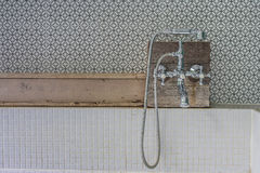 Vintage style shower head set on wooden shelf above bathtub in outdoor bathroom. Royalty Free Stock Image