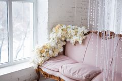 Vintage style sofa decorated with flowers in loft interior room with big window. Vintage style sofa decorated with flowers in loft interior room with big window Royalty Free Stock Image