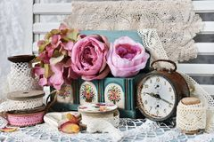 Vintage style still life with laces,flowers and alarm clock stock photography