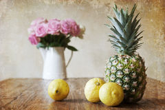 Vintage style still life picture with pineapple. Vintage style still life picture of a pineapple with three lemons on a wooden table and a rose bouquet in the stock photography