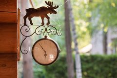 Vintage style street clock with metal deer sign hanged on a wooden log wall with green park or backyard on the background Royalty Free Stock Images
