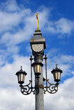 Vintage style street light across blue sky with clouds. Royalty Free Stock Image