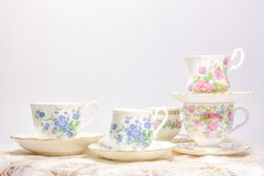 Attractive fine bone china tea cups on light background. Vintage style tea party cups and saucers with flowers and lace in soft pink and blue colors stock photos