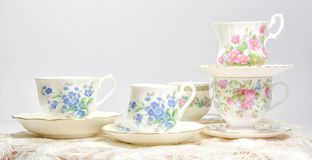 Attractive fine bone china tea cups on light background. Vintage style tea party cups and saucers with flowers and lace in soft pink and blue colors stock photo