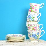 Attractive fine bone china tea cups on blue background. Vintage style tea party cups and saucers with flowers and lace in soft pink and blue colors on a square royalty free stock photography