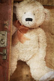 Vintage-style teddy bear and old suitcase Stock Photos