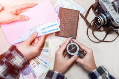Vintage Style Travel planning Composition with two People. Young Couple preparing for Journey holding Compass and Boarding Pass with Passports Cash Notes and Royalty Free Stock Image