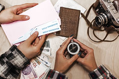 Vintage Style Travel planning Composition with two People. Young Couple preparing for Journey holding Compass and Boarding Pass with Passports Cash Notes and Royalty Free Stock Images