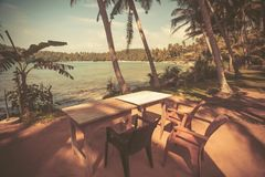 Vintage style view of table on ocean beach with coconut trees around. Tropical landscape at resort. Vintage style view of table on ocean beach with coconut Royalty Free Stock Photography